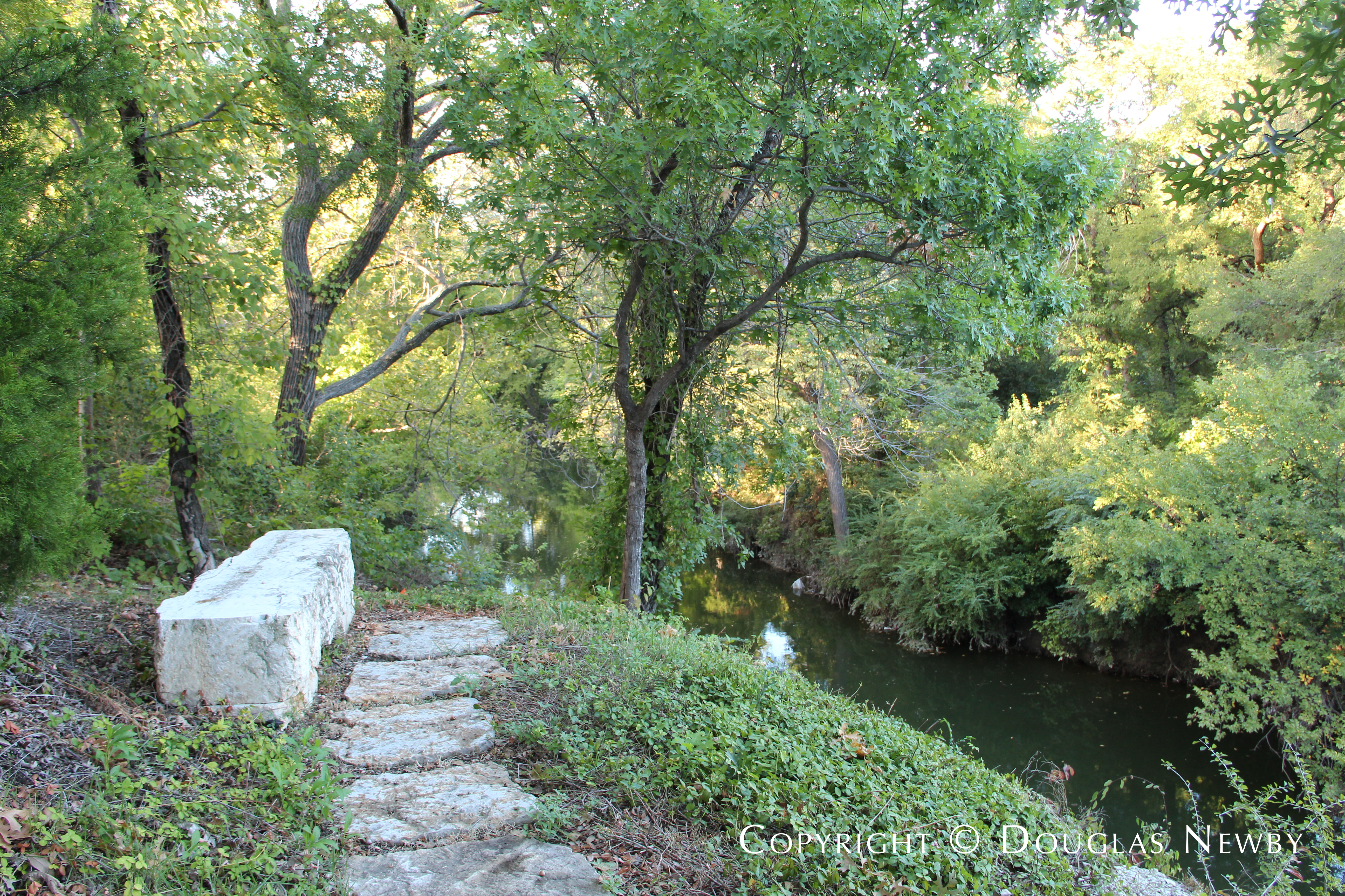 Stone Bench Set in Rugged Terrain Close to White Rock Creek on Boundary of the Glen Abbey Neighborhood
