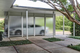 Floating carport with translucent panels on one side and storage along the other side